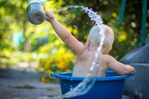 happy baby in a tiny bucket